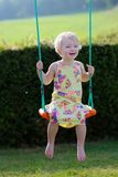 Cute preschooler girl swinging outdoors Stock Photo