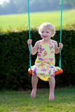 Cute preschooler girl swinging outdoors Stock Images