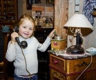 Cute preschooler girl talking by old vintage retro telephon. Closeup portrait royalty free stock photo