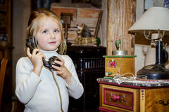 Cute preschooler girl talking by old vintage retro telephon. Closeup portrait stock photography