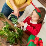 Cute preschooler girl wearing reindeer antlers and her mother making christmas wreath in living room. Christmas family fun. Cute preschooler girl wearing royalty free stock photography
