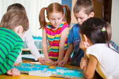 Cute preschoolers plaing game on table Royalty Free Stock Photography