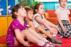 Cute preschoolers sitting on floor and listening Stock Photos