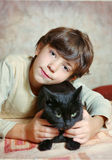 Cute preteen boy with black cat on the table Royalty Free Stock Photo