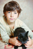 Cute preteen boy with black cat on the table Stock Photography