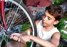 Cute preteen boy make rapairment of his bisycle Royalty Free Stock Images