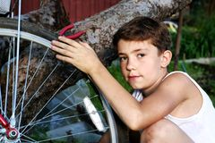Cute preteen boy make rapairment of his bisycle Royalty Free Stock Image