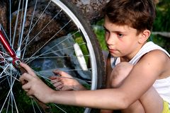 Cute preteen boy make rapairment of his bisycle Royalty Free Stock Photos