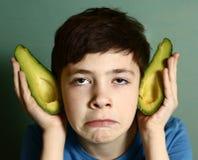 Cute preteen boy performing elf with avocado half Royalty Free Stock Images