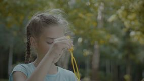 Cute preteen girl blowing soap bubbles in park stock video