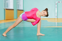 Cute preteen girl doing stretching exercise on mat. In school gymnasium Stock Image