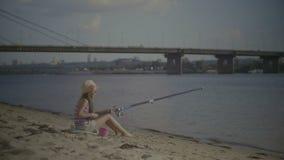 Cute preteen girl fishing on river bank stock video