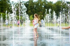 Cute preteen girl playing in fountains on newly renovated Lukiskes Square in Vilnius, Lithuania. Child having fun with water on stock photo
