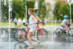 Cute preteen girl playing in fountains on newly renovated Lukiskes Square in Vilnius, Lithuania. Child having fun with water on stock photos