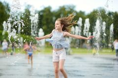 Cute preteen girl playing in fountains on newly renovated Lukiskes Square in Vilnius, Lithuania. Child having fun with water on stock image