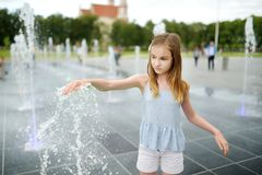 Cute preteen girl playing in fountains on newly renovated Lukiskes Square in Vilnius, Lithuania. Child having fun with water on royalty free stock image