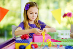 Cute preteen girl wrapping gifts in colorful wrapping paper. Stock Photo