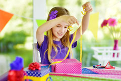 Cute preteen girl wrapping gifts in colorful wrapping paper. Adorable child wrapping birthday presents. Family fun Royalty Free Stock Images