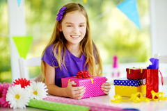 Cute preteen girl wrapping gifts in colorful wrapping paper. Adorable child wrapping birthday presents. Family fun Stock Image
