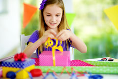 Cute preteen girl wrapping gifts in colorful wrapping paper. Adorable child wrapping birthday presents. Family fun Royalty Free Stock Image