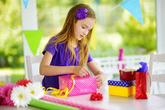 Cute preteen girl wrapping gifts in colorful wrapping paper. Royalty Free Stock Images