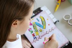 Cute preteen little girl writing her dreams in diary. Royalty Free Stock Photography
