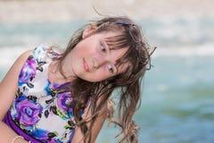 Cute preteen long hair girl on riverbank Royalty Free Stock Image