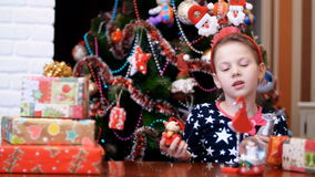 Cute pretty blonde girl with a pink bow in her hair, in a festive beautiful dress is playing with a toy Christmas deer stock footage