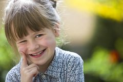 Cute pretty child girl with gray eyes and fair hair smiling in camera outdoors on blurred sunny green and yellow bright bokeh. Background stock images