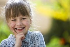 Cute pretty child girl with gray eyes and fair hair smiling in camera outdoors on blurred sunny green and yellow bright bokeh. Background stock photography