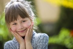 Cute pretty child girl with gray eyes and fair hair smiling in camera outdoors on blurred sunny green and yellow bright bokeh. Background stock photo