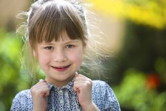 Cute pretty child girl with gray eyes and fair hair smiling outdoors on blurred sunny summer green and yellow bright bokeh. Background stock image