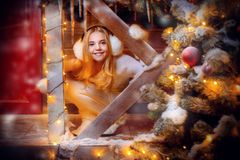 Happy young girl. Cute and pretty girl is in front of her house decorated for Christmas. Merry Christmas and Happy New Year royalty free stock photos