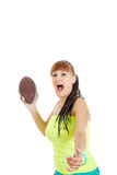 Cute pretty girl in green shirt throws brown rugby ball towards Royalty Free Stock Photo