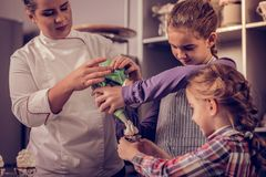 Cute pretty girls holding a piping bag together stock photos