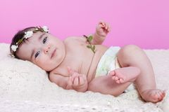 Cute, pretty, happy, chubby baby girl, naked or nude with diaper or nappy. On a fluffy blanket wearing a floral wreath headband or headdress. Four months old stock photography