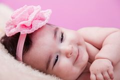 Cute, pretty, happy, chubby baby girl portrait with a big naughty smile. Naked or nude on fluffy blanket. Stock Photos