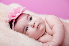 Cute, pretty, happy, chubby baby girl portrait, without clothes, naked or nude, on a fluffy blanket. Stock Image