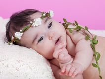 Cute, pretty, happy, chubby baby girl portrait, naked or nude, on a fluffy blanket. Wearing a floral wreath headband or headdress. Looking up. Four months royalty free stock photo