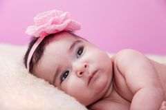 Cute, pretty, happy, chubby baby girl serious portrait, naked or nude, on a fluffy blanket. Royalty Free Stock Photography