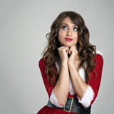 Cute pretty imaginative Santa girl looking up contemplating Stock Photo