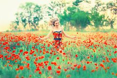 Cute pretty lady with blond hair in a short dress plays in a wide poppy field, as if in childhood, runs and dances stock image