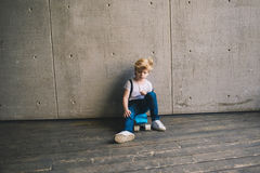 Little boy sitting on a skateboard at a wall. Cute and pretty little boy sitting on a skateboard at a wall Stock Photography