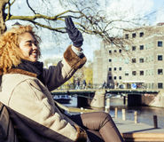 Cute pretty mulatto woman waving and smiling welcoming friends, streets of Amsterdam Royalty Free Stock Photo