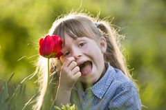 Cute pretty smiling child girl with gray eyes and long hair with bright red tulip flower on blurred sunny green bokeh background. Love to nature concept stock photography