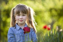 Cute pretty smiling child girl with gray eyes and long hair with bright red tulip flower on blurred sunny green bokeh background. stock photo