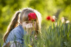 Cute pretty smiling child girl with gray eyes and long hair with bright red tulip flower on blurred sunny green bokeh background. Love to nature concept royalty free stock images