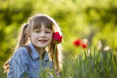 Cute pretty smiling child girl with gray eyes and long hair with bright red tulip flower on blurred sunny green bokeh background. stock image