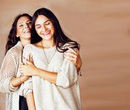 Cute pretty teen daughter with mature mother hugging, fashion st. Yle brunette makeup close up tann mulattos, warm colors close up stock images