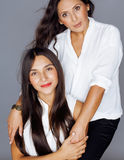 Cute pretty teen daughter with mature mother hugging, fashion style brunette makeup Royalty Free Stock Photos
